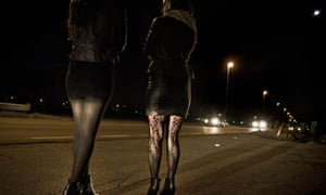 Two women in short skirts solicit for business on the street at night