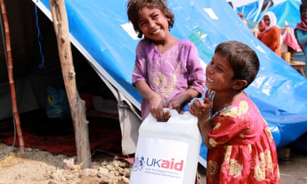 Children carry a bottle of detergent supplied by UKaid from the British government, as part of the UK's response to the floods in Pakistan.