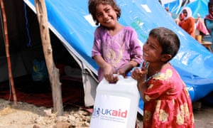 Children in Pakistan carrying a bottle of detergent supplied by UKaid