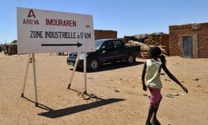 A resident walking past Areva's uranium symbol in a village near Arlit, Niger