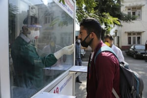 A health worker collects a nasal swab sample to test for Covid-19 at a government hospital in Jammu, India.