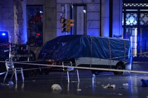The van who ploughed into the crowd, killing at least 13 people and injuring around 100 others is towed away from the Rambla in the early hours