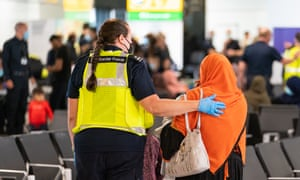 """Home Secretary Priti Patel Greets Afghan Evacuees Arriving at HeathrowLONDON, ENGLAND - AUGUST 26: A member of Border Force staff assists a female evacuee as refugees arrive from Afghanistan at Heathrow Airport on August 26, 2021 in London, England. Ministry of Defence figures put the number of people evacuated by the UK since August 13 at 9,226, but there are thousands feared to be remaining. Foreign Secretary Dominic Raab has said the UK will use """"every hour"""" left to evacuate people from Afghanistan as he declined to rule out British troops having to leave by the end of Friday. (Photo by Dominic Lipinski - WPA Pool/Getty Images)"""
