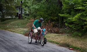 Residents of the Mount Pleasant neighborhood in Cleveland, Ohio bike down a street littered with abandoned homes.