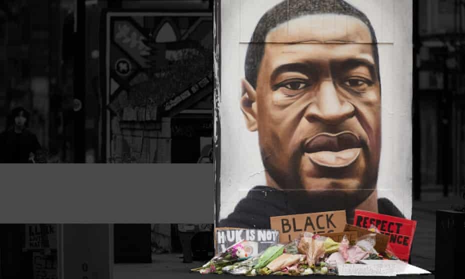 Flowers and tributes surrounding street artist Akse's mural of George Floyd