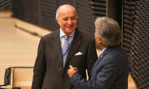 Laurent Fabius speaks to a colleague at the Katowice climate change conference