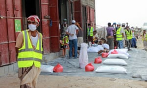 Employees of the World Food Programme (WFP) distribute relief items to displaced Yemenis in the capital Sanaa