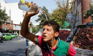 An Iranian street vendor pours water on his face to cool off during a heatwave in Tehran, Iran, 02 August 2015.