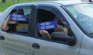 """A protest against Brazil's President Jair Bolsonaro's government in Sao PauloPeople hold signs reading """"+ Vaccine - Bolsonaro"""" during a motorcade to protest against Brazil's President Jair Bolsonaro's government in Sao Paulo, Brazil February 20, 2021."""