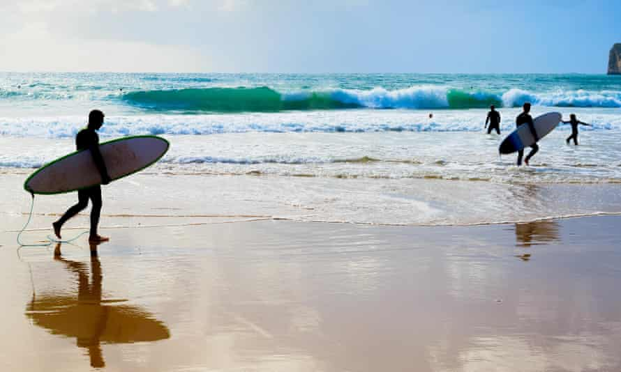 Surfers with surfboards on the beach in the Algarve, Portugal