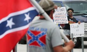 A protester faces off with hundreds of pro-Confederate flag supporters during a flag rally.