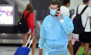 A man in personal protective equipment at a baggage collection area at Tullamarine airport in Melbourne on Friday.