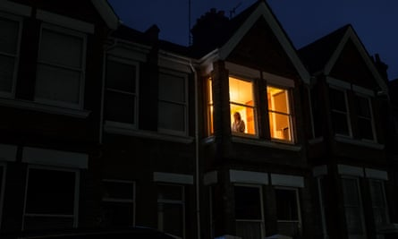 A house in darkness with Kate Edgley standing in the one lit upstairs window