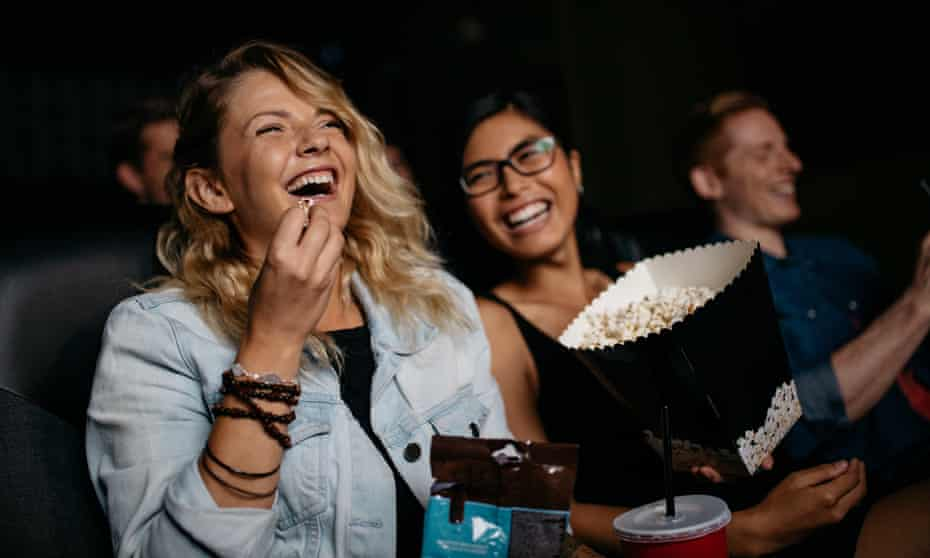 Two laughing women at a cinema eating popcorn