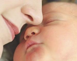 Newborn baby boy (0-3 months) sleeping on mother's shoulder, close-up
