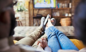 Couple holding hands, watching TV in living room