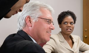 Woman looking at men whispering in office