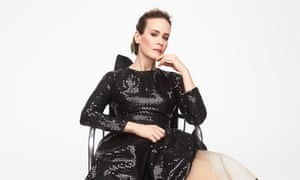 Sarah Paulson in a shiny black dress leaning back in a chair