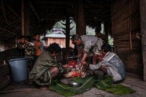 Men prepare a freshly slain pig for the new day's feast.