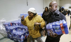 R&B singer Kem helps carry bottled water after donating $10,000 to the Salvation Army to aid efforts to provide bottled water to residents of Flint, Michigan.