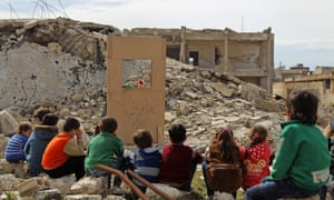 Children watch a puppet show at a makeshift theatre in the rubble of collapsed buildings in Idlib.