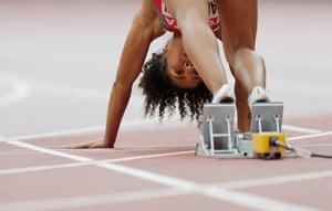 Switzerland's Mujinga Kambundji puts her feet in the blocks for the start of a women's 100m heat.