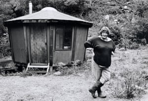Woman in gumboots stands in front of hut in the bush
