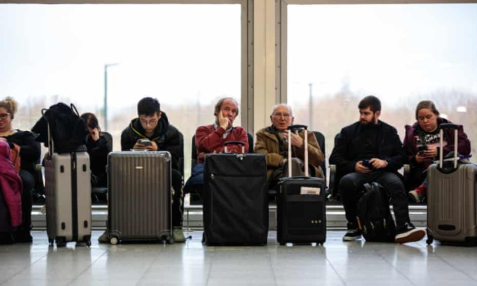Passengers wait at Gatwick airport on Friday. a