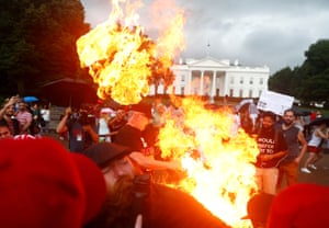 Demonstrators burn a national flag in front of the White House