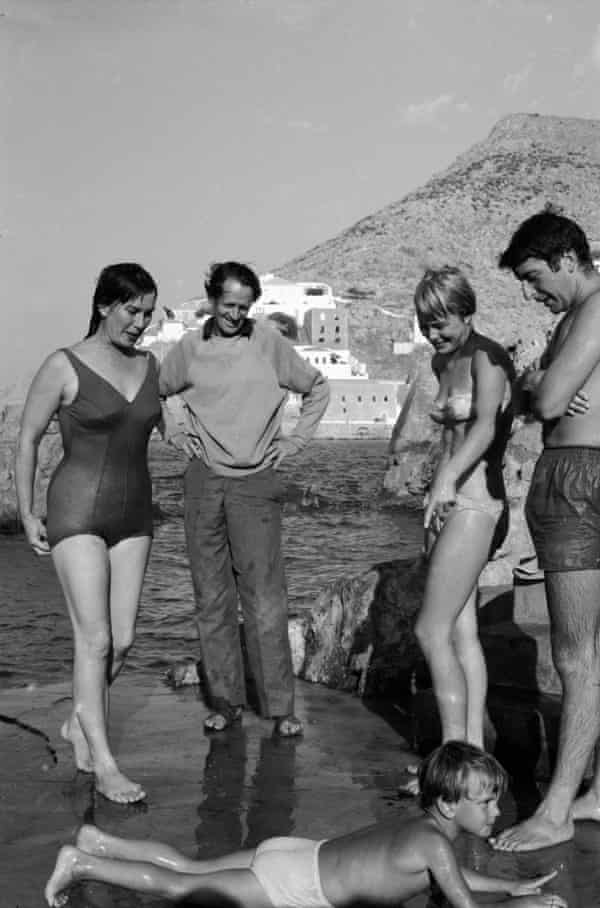 George Johnston and Charmian Clift (left) watch their son Jason crawl on the sand at Hydra in Greece in 1960, with Marianne Jensen and Leonard Cohen (right).