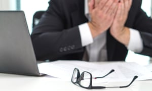 Stressed businessman covering face with hands in office
