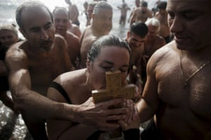 A woman kisses a wooden crucifix retrieved from the water in Faliro, Athens