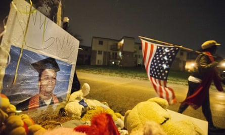 A woman carries an American flag past a high school graduation photo of Michael Brown at a memorial in Ferguson.