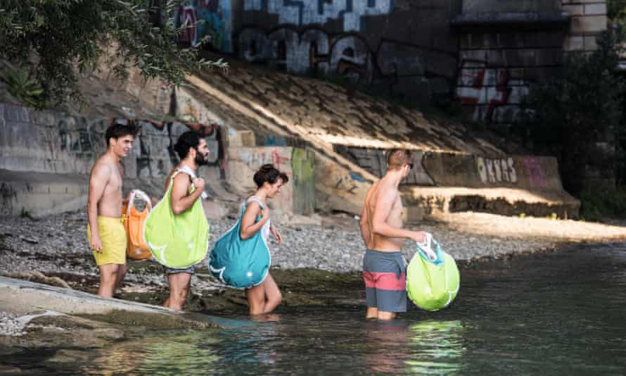 A group of male and female swimmers enter the Rhine river in Basel, Switzerland, carrying their possessions in brightly coloured waterproof Wickelfisch bags.