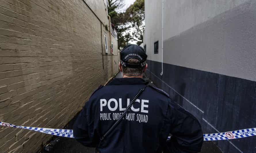 A Police officer watches over a raid in Surry Hills in inner Sydney. Counter-terrorism police raided four houses across Sydney on Saturday night and arrested four men over an alleged terror plot that involved blowing up an aircraft.