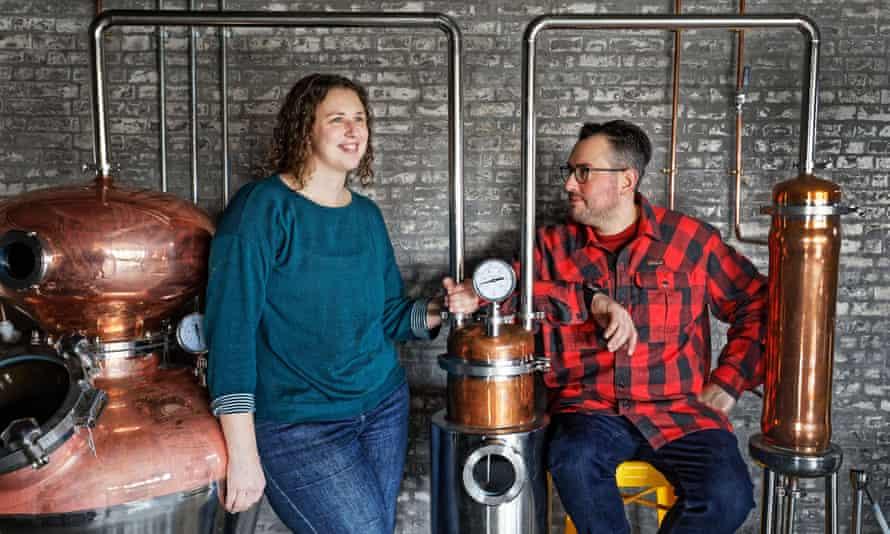 Ellen Wakelam and Alex Jungmayr, smiling beside their distilling equipment
