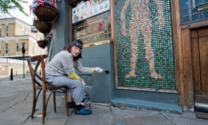 """Sandra Esquilant, landlady of the Golden Heart pub in Shoreditch, London. Sandra was touching up the pub with Farrow and Ball 'Downpipe' for the VE celebrations. She had also put up some bunting outside. """"I'm so bored of this coronavirus lockdown. I just wanted to make an effort""""."""