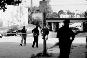 Police and detectives at a shooting scene on Patterson Park Avenue on 22 July 2013