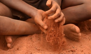 A young Aboriginal boy plays in the red sand