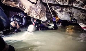 Thai navy officers work inside the cave complex where the boys are trapped.