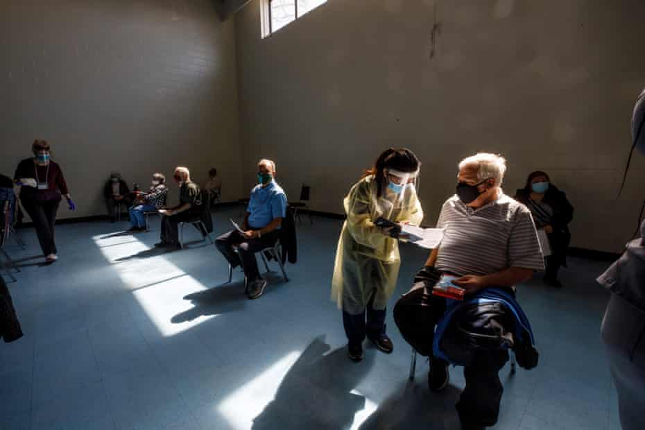 Nurse Priscilla Policar fills in paper work with community members inside a gymnasium at St Fidelis Parish.