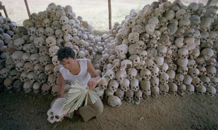 A man cleans a skull near a mass grave at the Chaung Ek torture camp run by the Khmer Rouge.