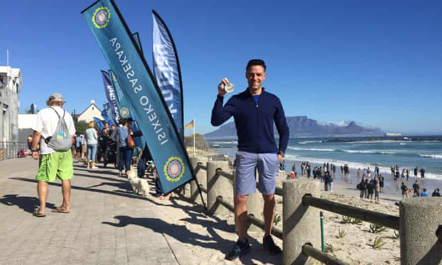 Writer Graham Little shows off his medal after completing the Freedom Swim in Cape Town, South Africa.