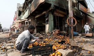 A man collects the remains of damaged fruit in a row of burnt-out shops in north-east Delhi on 28 February.