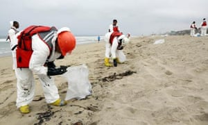A crew cleans up a beach after balls of tar washed ashore in Manhattan beach, California, on Thursday.