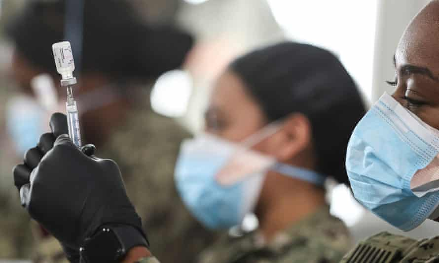 US navy personnel prepare doses of the Pfizer vaccine for administration