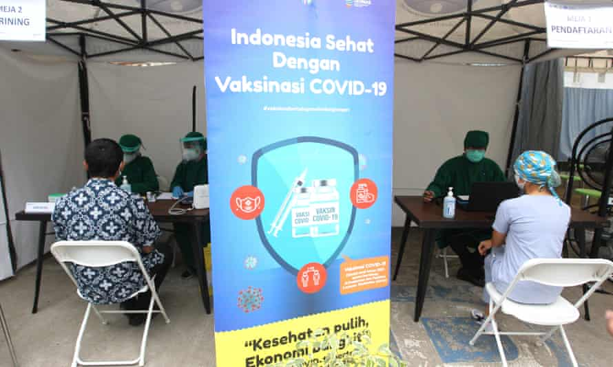 Health workers wait to be vaccinated at a facility in Jakarta