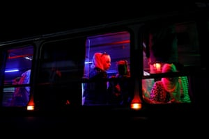 People travel in a bus after arriving at a recently opened international fair on the outskirts of the city.