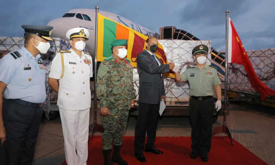 Wan Dong (right), defense attaché at the Chinese embassy in Sri Lanka, and Kamal Gunaratne (second from right), Sri Lankan secretary-general of defense, fists handing over a batch of Sinopharm vaccine.