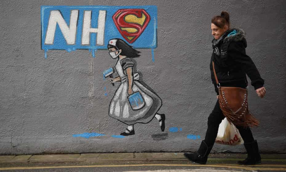 Graffiti depicting the badge of the Superman and Superwoman, and an NHS logo above street art of a nurse, on a wall in Pontefract, West Yorkshire